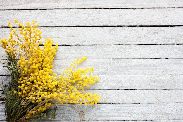 Een boeket van mimosa op een blauwe houten achtergrond, springt bloeiende takjes op een oude houten achtergrond op Premium Foto