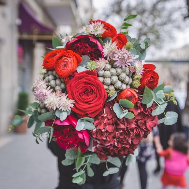 Een boeket van rode rozen, pioenrozen en groene decoratieve bloemen met bladeren Gratis Foto