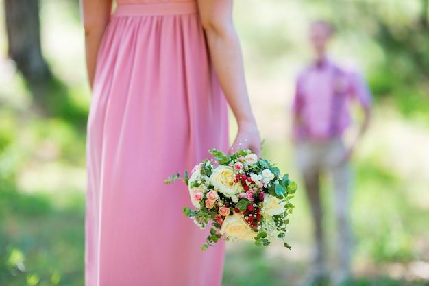 Een boeket verse bloemen in handen nesta in een roze jurk close-up Premium Foto