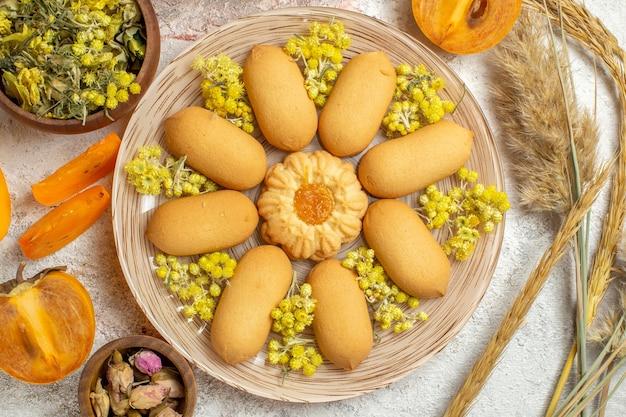 Een bord met koekjes en droge bloemen en emmers en palmen op marmer Gratis Foto