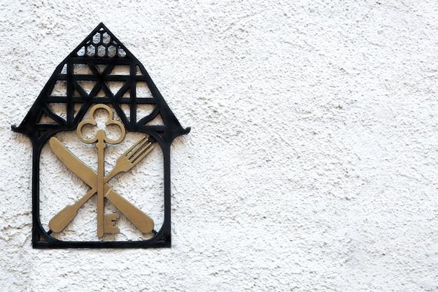 Een bord op de muur met het beeld van het huissleutelmes en de vork. Premium Foto