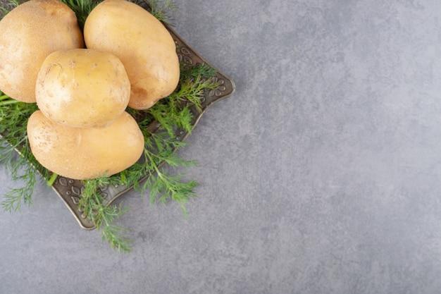 Een bord van ongekookte aardappelen met verse dille. Gratis Foto