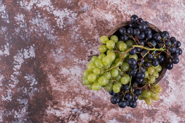 Een bos groene en rode druiven op het marmer Gratis Foto