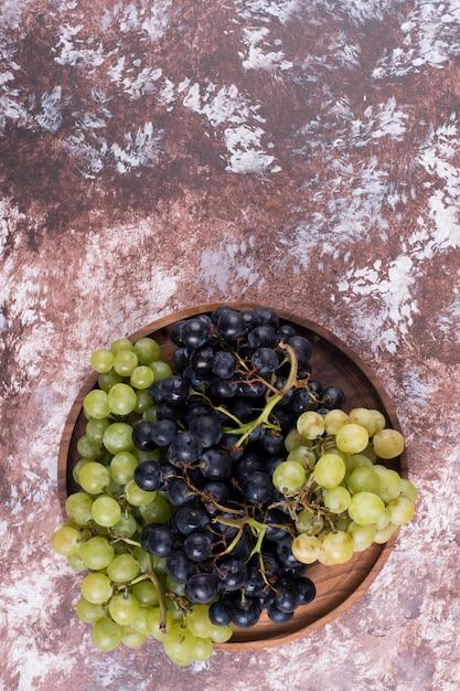 Een bos van groene en rode druiven in een houten schotel Gratis Foto