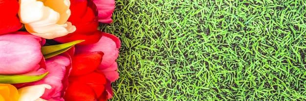 Een bos van heldere verse kleurrijke tulpen op een gras achtergrond. Premium Foto