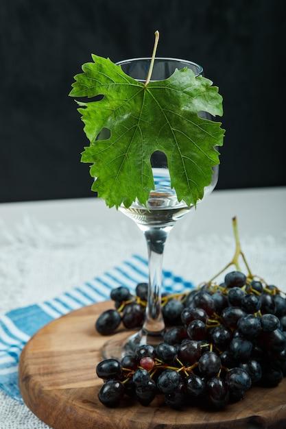 Een bos van zwarte druiven en een glas wijn met blad op witte lijst Gratis Foto