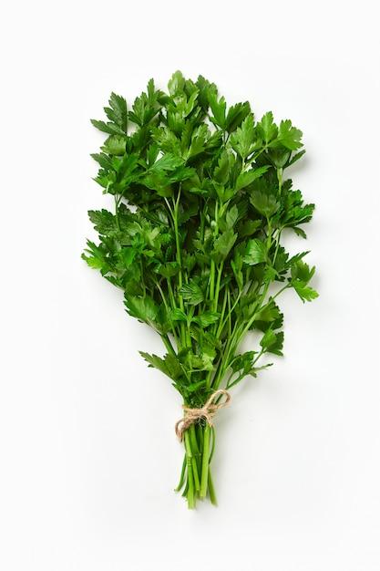 Een bosje peterselie geïsoleerd. groene frisse, ecologische peterselie gebonden door een ecokabel. Premium Foto
