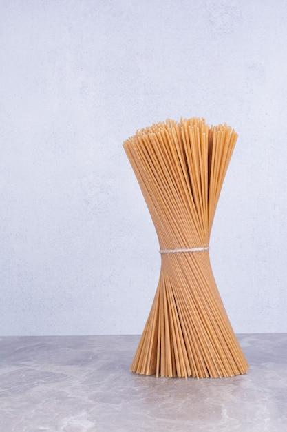 Een bosje rauwe zelfgemaakte spaghetties op de grond Gratis Foto