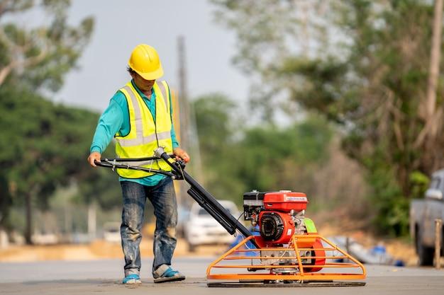 Een bouwvakker die een natte concret giet bij wegenbouwplaats Premium Foto