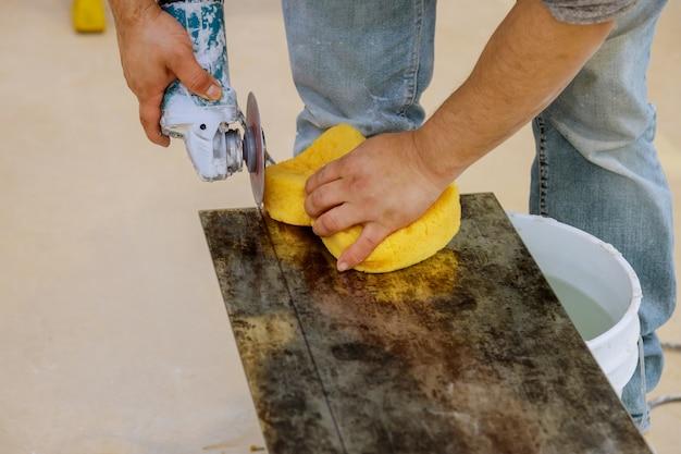 Een bouwvakker die een tegel snijdt die molen gebruikt Premium Foto