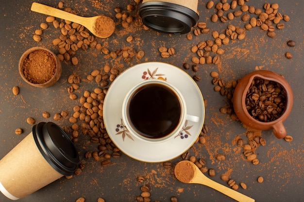 Een bovenaanzicht bruine koffiezaden met choco-repen en kopje koffie Gratis Foto