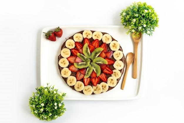 Een bovenaanzicht choco aardbei dessert lekker zoet versierd verse bananen en kiwi's samen met planten verspreid over de witte achtergrond exotische fruitcake Gratis Foto