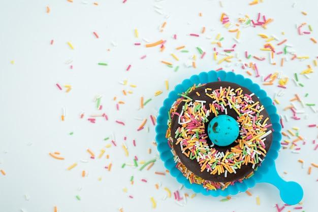 Een bovenaanzicht chocolade donut met kleine kleurrijke snoepjes op wit bureau, snoep kleur snoepjes Gratis Foto