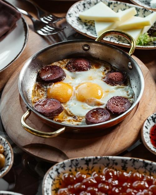Een bovenaanzicht eieren met worst samen met kaas op het bruine houten bureau eten maaltijd ontbijt Gratis Foto