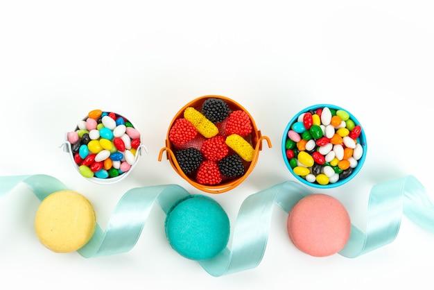 Een bovenaanzicht franse macarons samen met kleurrijke snoepjes en marmelades op wit, cakekoekje kleur Gratis Foto