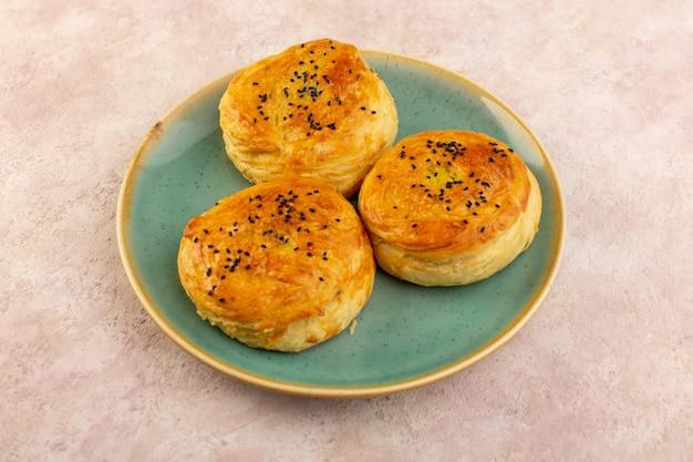 Een bovenaanzicht gebakken qogals rond gevormd lekker warm vers uit de oven in groene plaat Gratis Foto