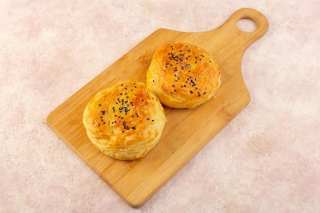 Een bovenaanzicht gebakken qogals rond gevormd lekker warm vers uit de oven op het bruine houten bureau Gratis Foto
