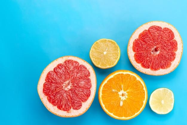 Een bovenaanzicht gesneden citrusvruchten grapefruits sinaasappelen en citroenen op blauw bureau, citrusvruchtensap Gratis Foto