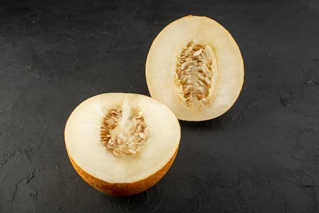 Een bovenaanzicht gesneden verse meloen zoete pulpy mellow geïsoleerd op donker Gratis Foto