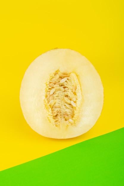 Een bovenaanzicht gesneden verse meloen zoete pulpy mellow geïsoleerd op groen-geel Gratis Foto