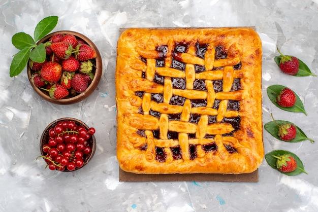 Een bovenaanzicht heerlijke aardbeientaart met aardbeigelei binnen, samen met verse aardbeien en veenbessen op de grijze bureaucake Gratis Foto