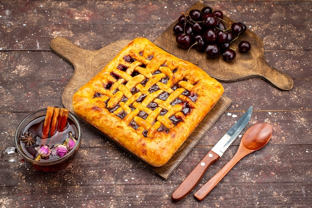 Een bovenaanzicht heerlijke aardbeientaart met aardbeigelei kersen en thee op de houten bureau cake koekjessuiker Gratis Foto