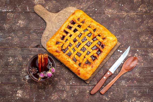 Een bovenaanzicht heerlijke aardbeientaart met aardbeigelei samen met thee op de houten koekjessuiker van het bureau Gratis Foto