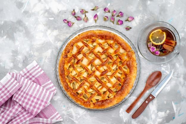 Een bovenaanzicht heerlijke appeltaart met hete thee en bloemen cake koekjes suiker thee Gratis Foto