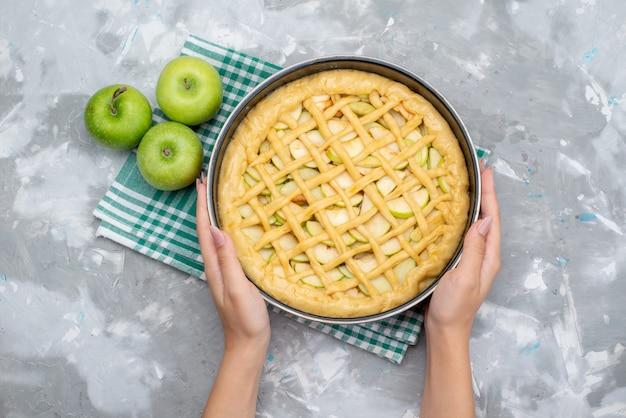 Een bovenaanzicht heerlijke appeltaart ronde gevormd binnen pan met verse groene appels cake koekje Gratis Foto
