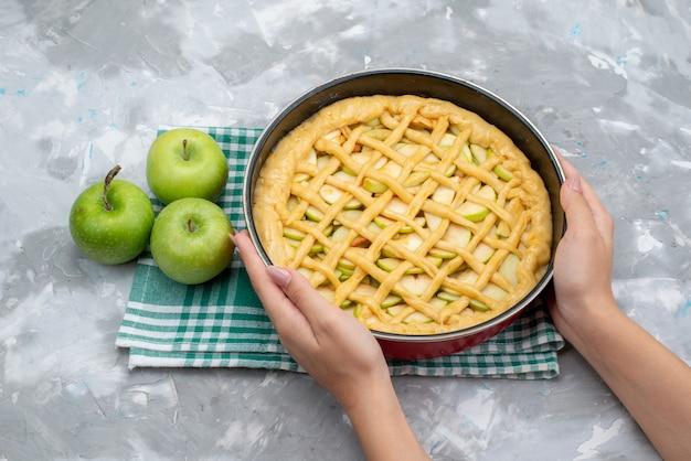 Een bovenaanzicht heerlijke appeltaartronde gevormd in de pan die de oven in gaat met verse groene appels op het lichte bureau cakekoekje Gratis Foto