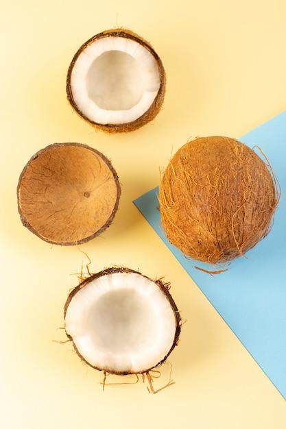Een bovenaanzicht hele kokosnoten en gesneden melkachtig fris mellow geïsoleerd op de crème-iced-blauw gekleurd Gratis Foto