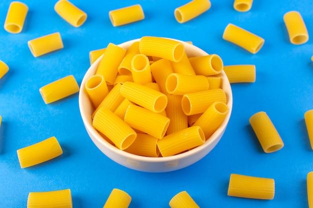 Een bovenaanzicht italia droge pasta vormde kleine gele rauwe pasta in crèmekleurige ronde kom geïsoleerd op de blauwe achtergrond italiaanse spaghetti food pasta Gratis Foto