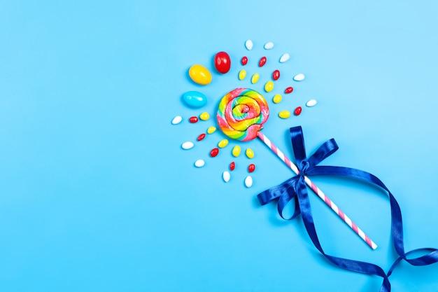 Een bovenaanzicht kleurrijke lolly met roze-witte stok blauwe boog en veelkleurige snoepjes op de blauwe achtergrond verjaardagsfeestje Gratis Foto
