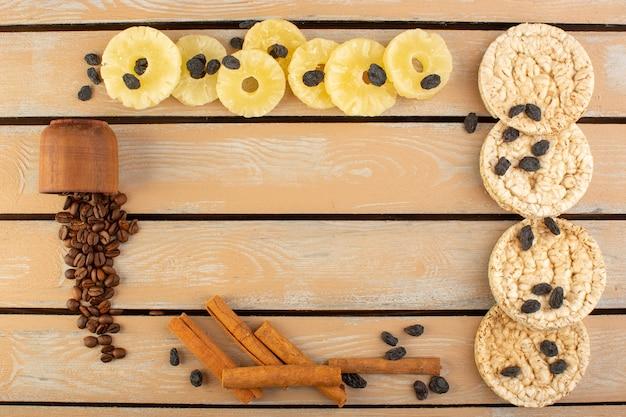 Een bovenaanzicht koffie zaden met gedroogde ananas kaneel en crackers op de crème rustieke tafel koffiezaad drank foto graan Gratis Foto