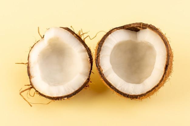 Een bovenaanzicht kokosnoten gesneden melkachtig fris mellow geïsoleerd op crème achtergrond tropische exotische fruit noot Gratis Foto