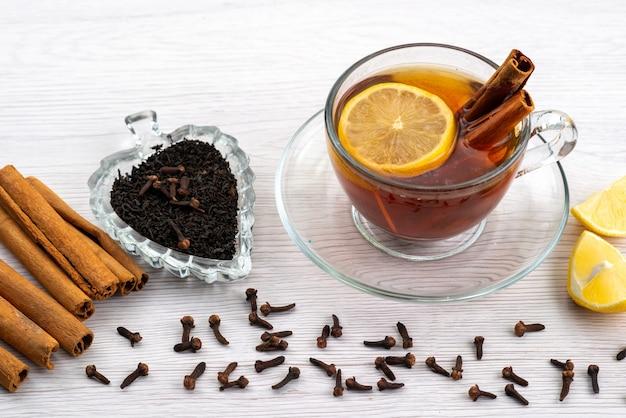 Een bovenaanzicht kopje thee met citroen en kaneel op wit, thee dessert snoep Gratis Foto