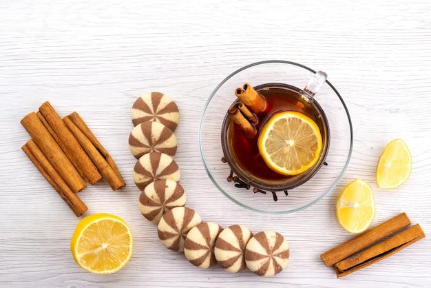 Een bovenaanzicht kopje thee met citroenkoekjes en kaneel op wit, theedessert snoep Gratis Foto