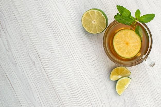 Een bovenaanzicht kopje thee met groene citroen op wit, vloeibaar drankje fruit Gratis Foto