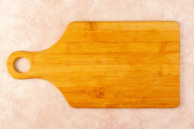 Een bovenaanzicht leeg houten bureau bruin geïsoleerd op de roze achtergrond houten boomtafel Gratis Foto