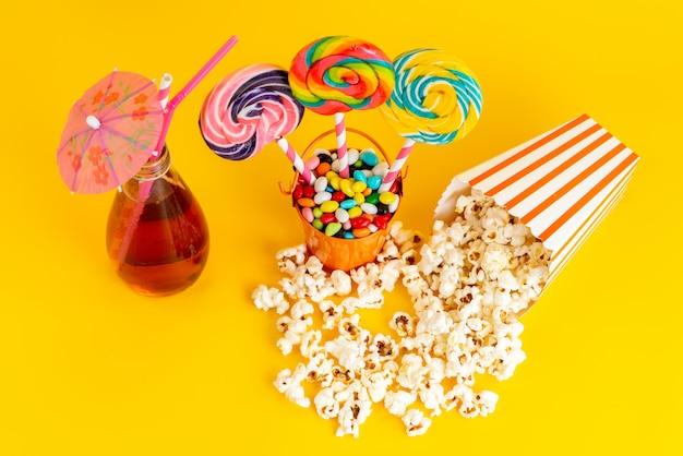 Een bovenaanzicht lollies en popcorn met cocktail en veelkleurige snoepjes op de gele achtergrond drink suiker confituur Gratis Foto