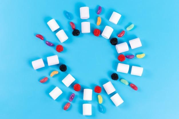 Een bovenaanzicht marshmallows en marmelade bekleed op blauw, suikerwerk kinderen cirkel Gratis Foto