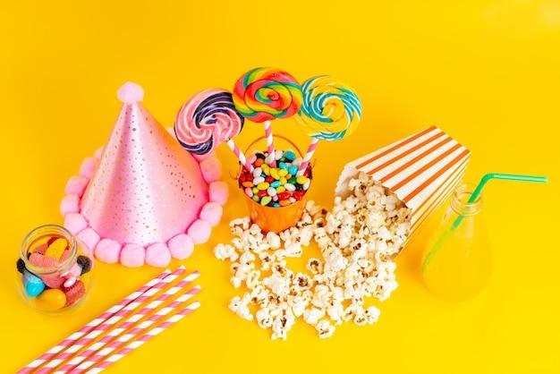 Een bovenaanzicht popcorn en snoep samen met roze grappige pet en cocktail Gratis Foto