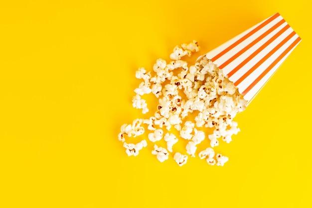 Een bovenaanzicht popcornpakket gezouten smakelijke verspreid over de gele achtergrond Gratis Foto