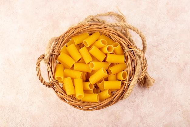 Een bovenaanzicht rauwe italiaanse pasta geel in een mandje samen met touwen op roze Gratis Foto