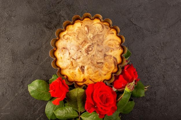 Een bovenaanzicht ronde zoete cake heerlijke en lekkere chocoladetaart in cake pan samen met rode rozen geïsoleerd op de grijze achtergrond suiker thee koekje bakken Gratis Foto