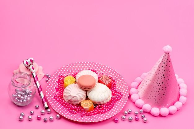 Een bovenaanzicht schuimgebakjes en macarons zoete en heerlijke taarten in plaat met verjaardag dop en verjaardagsfluitje op roze, cakek koekje Gratis Foto