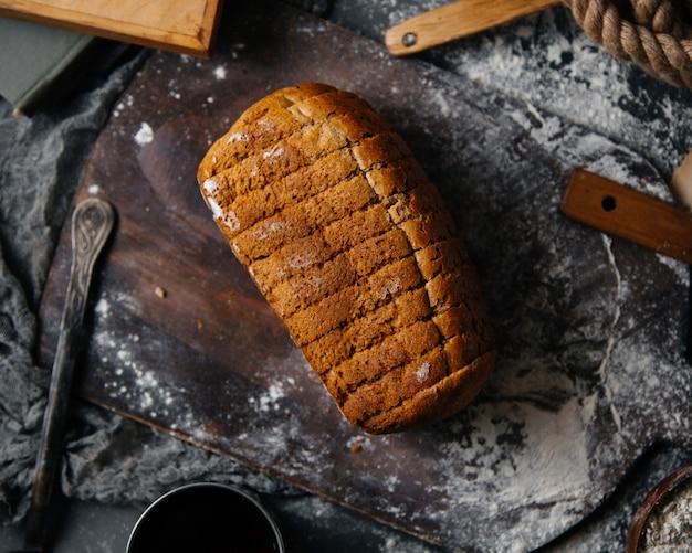 Een bovenaanzicht sneed grijs brood dat op het grijze deeg van de het voedselmaaltijd van het bureaubroodje wordt gebakken Gratis Foto