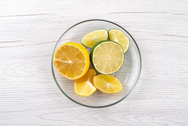 Een bovenaanzicht sneed zure citroen sappig in glazen kom op wit bureau, vruchtensap kleur Gratis Foto