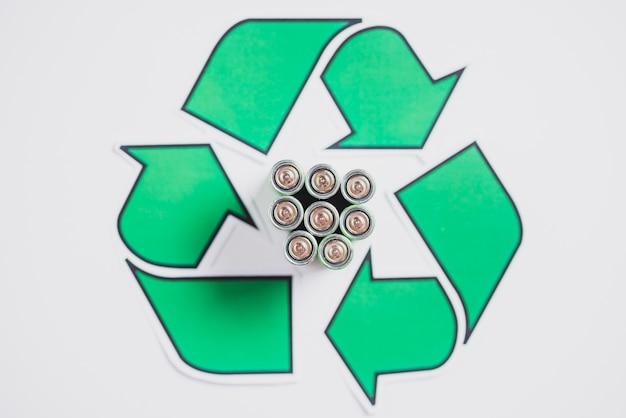 Een bovenaanzicht van batterijen in recycle pictogram op witte achtergrond Gratis Foto