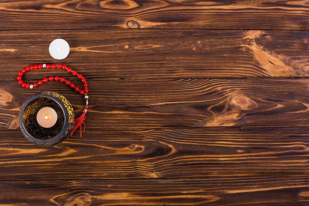Een bovenaanzicht van brandende kaars in de houder met heilige parels op houten bureau Gratis Foto